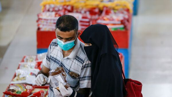 A couple wearing protective face masks and gloves shop at a supermarket amid concerns of the spread of the coronavirus disease (COVID-19), in Sanaa, Yemen May 11, 2020. - Sputnik International