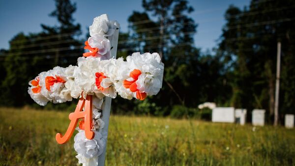A white and orange cross with an A on it stands stuck in the ground along highway 17 at the entrance of the Satilla Shores neighbourhood where Ahmaud Arbery, an unarmed young black man, was shot after being chased by a white former law enforcement officer and his son, at the Glynn County Courthouse in Brunswick, Georgia, U.S., May 8, 2020 - Sputnik International
