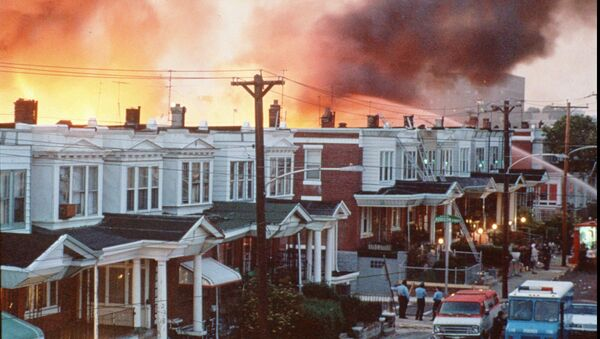 FILE--Row houses in Philadelphia burn after officials dropped a bomb on the MOVE house in this May 1985 photo from files. Ramona Africa, the lone adult survivor of the May 13, 1985 fire, and two other MOVE members sued the city of Philadelphia, and the former police and fire commissioners for financial damages in what was the first trial in court to address the MOVE bombing. The jury said Monday afternoon June 24, 1996, that it reached a verdict, but the result was not announced immediately.(AP Photo/files) - Sputnik International