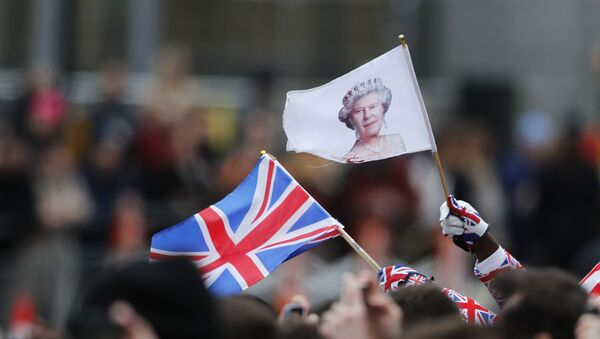 People wave a British union flag and a flag bearing the image of Britain's Queen Elizabeth II ahead of the annual Commonwealth Day service at Westminster Abbey in London, Monday, March 9, 2020 - Sputnik International