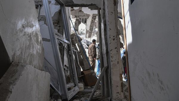 In this photo released by the Syrian official news agency SANA, people look at the rubble of a house that according to the Syrian authorities was attacked by an Israeli airstrike, in the Damascus suburbs of Hajira, Syria, Monday, April 27, 2020 - Sputnik International