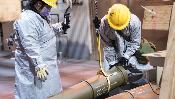 Two operators work together to place one of the last overpacked 8-inch projectiles containing nerve agent into a tray to begin the destruction process at the Blue Grass Chemical Agent-Destruction Pilot Plant May 9. The last GB 8-inch projectile was destroyed May 11, marking the complete destruction of an entire type of chemical weapon. - Sputnik International