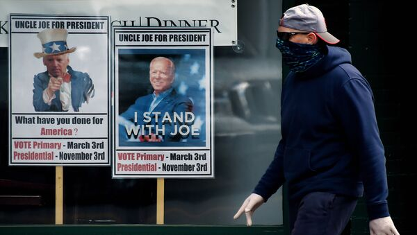 A man wearing a face mask walks past signs for Joe Biden's 2020 presidential campaign amid the coronavirus outbreak on May 11, 2020 in Alexandria, Virginia - Sputnik International