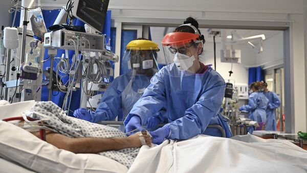 Members of the clinical staff wearing Personal Protective Equipment PPE care for a patient with coronavirus in the intensive care unit at the Royal Papworth Hospital in Cambridge, 5 May 2020 - Sputnik International