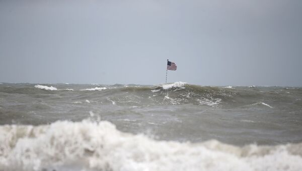 Waves crash in front of an American flag that is planted on a jetty during a high surf from the Atlantic Ocean, in advance of the potential arrival of Hurricane Dorian, in Vero Beach, Fla., Monday, Sept. 2, 2019. - Sputnik International