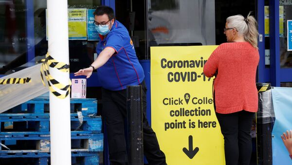 An employee wearing a protective face mask is seen with a customer at a Smyths in Wigan, following the outbreak of the coronavirus disease (COVID-19), Wigan, Britain, May 18, 2020.  - Sputnik International