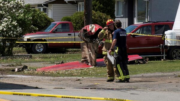 Fire officials talk in a residential neighbourhood street in front of the tail wreckage from a Royal Canadian Air Force Snowbirds jet after a member of the exhibition team crashed shortly after takeoff in Kamloops, British Columbia, Canada May 17, 2020. - Sputnik International