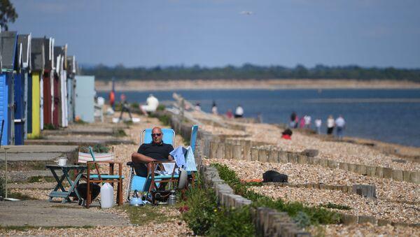 Мужчина во время отдыха на пляже в Южной Англии  - Sputnik International