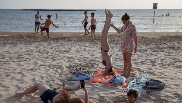 People enjoy the beach front in Tel Aviv, Israel, Saturday, May 16, 2020. Israeli authorities have recently begun loosening the restrictions of the coronavirus lockdown, the easing brought people out of their homes to enjoy the outdoors.  - Sputnik International
