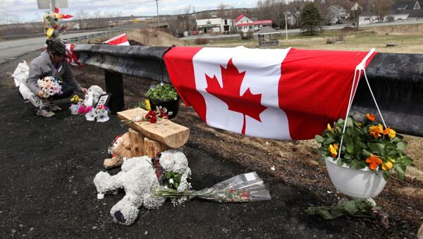 Krista Hughes adjusts flowers that had blown away from a makeshift memorial for Royal Canadian Mounted Police (RCMP) Constable Heidi Stevenson, who was shot dead during Sunday's killing spree that worked it's way across several Nova Scotian communities, in Shubenacadie, near Enfield, Nova Scotia, Canada April 22, 2020. - Sputnik International
