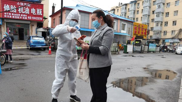 A worker in protective suit takes body temperature measurement of a woman following the coronavirus disease (COVID-19) outbreak in Jilin, Jilin province, China May 17, 2020. Picture taken May 17, 2020. cnsphoto via REUTERS   ATTENTION EDITORS - THIS IMAGE WAS PROVIDED BY A THIRD PARTY. CHINA OUT. - Sputnik International