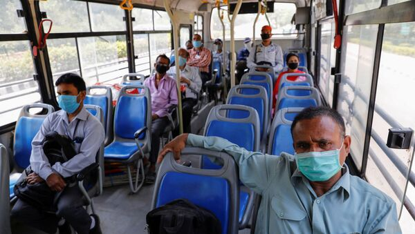 People wearing face masks travel in a bus, maintaining social distancing after few restrictions were lifted during an extended lockdown to slow the spread of the coronavirus disease (COVID-19) in New Delhi, India, May 20, 2020.  - Sputnik International