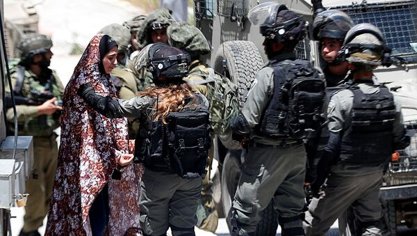 A Palestinian woman cries as she is stopped by Israeli forces after an Israeli soldier was killed by a rock thrown during an arrest raid, in Yabad near Jenin in the Israeli-occupied West Bank May 12, 2020 - Sputnik International