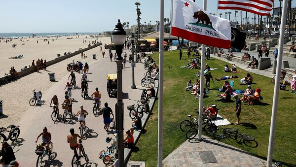 People sit at the beach as cyclists ride bicycles on Memorial Day weekend during the outbreak of the coronavirus disease (COVID-19) in Huntington Beach, California, U.S., May 23, 2020. - Sputnik International