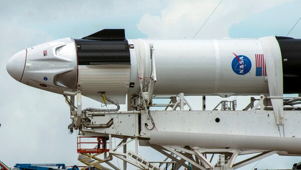 Crews work on the SpaceX Crew Dragon, attached to a Falcon 9 booster rocket, as it sits horizontal on Pad39A at the Kennedy Space Center in Cape Canaveral, Florida, U.S. May 26, 2020. - Sputnik International