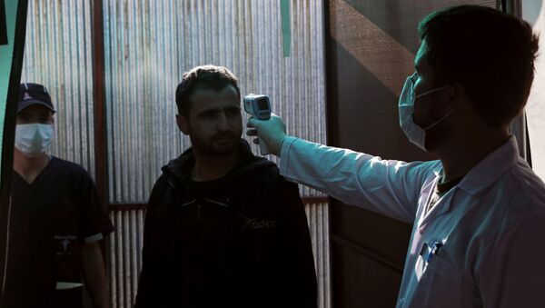A Syrian man has his temperature checked at the entrance of a quarantine centre, where those entering from Turkey are carefully monitored as a preventive measure against the spread of the coronavirus disease (COVID-19), in the town of Jisr al-Shughour in Idlib province, Syria, 30 April 2020 - Sputnik International