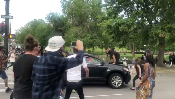 A protester is seen on top of a vehicle speeding through a protest held nationally, following the death of African-American George Floyd who was seen in graphic video footage gasping for breath as a white officer knelt on his neck, in Minneapolis, Minnesota, in Denver, Colorado, May 28, 2020 - Sputnik International