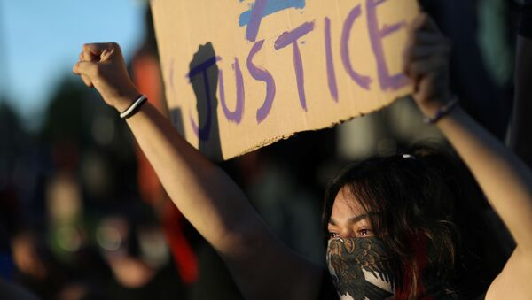 A protester holds a sign as protesters continue to rally against the death in Minneapolis police custody of George Floyd, in Minneapolis, Minnesota, U.S. May 30, 2020. - Sputnik International