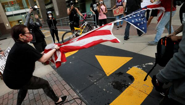 Protesters rip apart a US flag during nationwide unrest following the death in Minneapolis police custody of George Floyd, in Raleigh, North Carolina, US. - Sputnik International