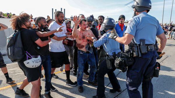 Protesters hand over to police the driver (C) of a tanker truck who drove into hundreds of protesters marching on 35W northbound highway during a protest against the death in Minneapolis police custody of George Floyd, in Minneapolis, Minnesota. - Sputnik International