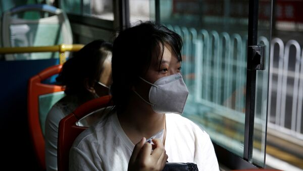 Woman wearing a face mask rides on a bus with her husband and friends to a shopping mall to look for a job in Beijing - Sputnik International