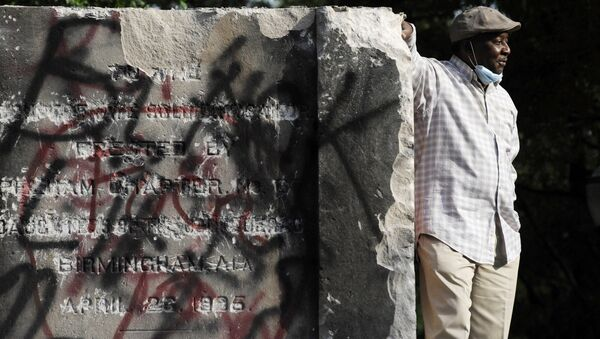 Robert Walker poses for a photograph on the remains of a Confederate memorial that was removed overnight in Birmingham, Ala., on Tuesday, June 2, 2020 - Sputnik International
