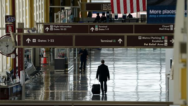 FILE PHOTO: A lone passenger walks through Reagan National airport as the outbreak of the novel coronavirus (COVID-19) pandemic continues to keep airline travel at minimal levels and the U.S. economy contracts in the first quarter at its sharpest pace since the Great Recession, in Washington, U.S. April 29, 2020 - Sputnik International