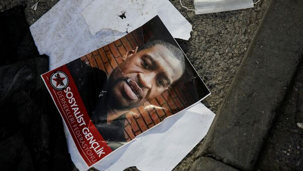 A portrait of George Floyd, who died in police custody in  Minneapolis, U.S., lies on the ground next to a protective face mask after a scuffle took place during a protest in Istanbul, Turkey, June 2, 2020 - Sputnik International