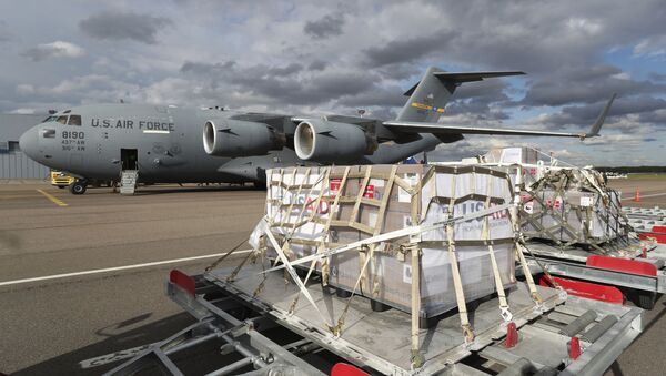A tractor pulls the first batch of medical aid from the United States, including 50 ventilators as a donation to help the country tackle the coronavirus outbreak, from a US Air Force C-17 Globemaster transport plane upon its landing at Vnukovo International Airport outside Moscow, Russia, 21 May 2020. - Sputnik International