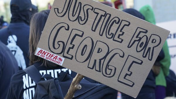 A poster with the inscription 'Justice for George' and 'Antifa on the offensive' is held by a protestor during a demonstration under the motto Youth Day - Fight for your future - Sputnik International