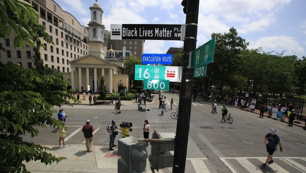 With St. John's Church in the background, people walk under a new street sign on Friday, June 5, 2020, in Washington. The section of 16th street in front of the White House is now officially 'Black Lives Matter Plaza,' District of Columbia Mayor Muriel Bowser tweeted. The black and white sign was put up to mark the change - Sputnik International