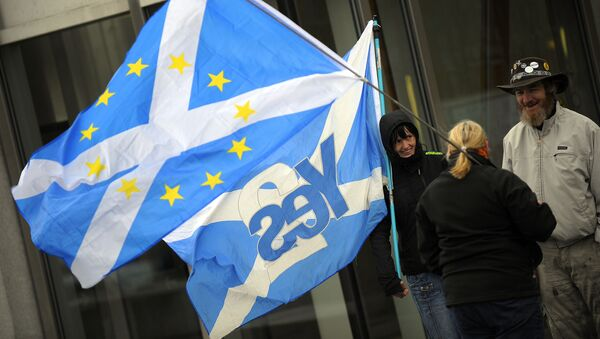 This picture shows pro-independence campaigners with one holding a 'yes' to independence flag and another holding a Saltire flag with EU logo design, outside the Scottish Parliament b - Sputnik International