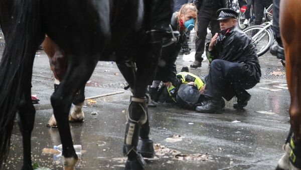 A colleague attends to a police officer who was injured when falling of a horse during scuffles with demonstrators at Downing Street during a Black Lives Matter march in London, Saturday, June 6, 2020, as people protest against the killing of George Floyd by police officers in Minneapolis, USA. - Sputnik International