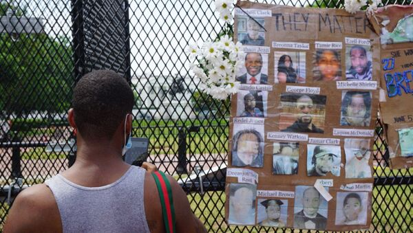 A man stands next to photos of victims of police brutality displayed on a metal fence during a protest near the White House in Washington DC, US, 06.06.2020. - Sputnik International
