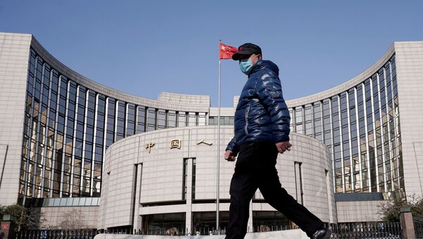 A man wearing a mask walks past the headquarters of the People's Bank of China, the central bank, in Beijing, China, as the country is hit by an outbreak of the new coronavirus, February 3, 2020. - Sputnik International