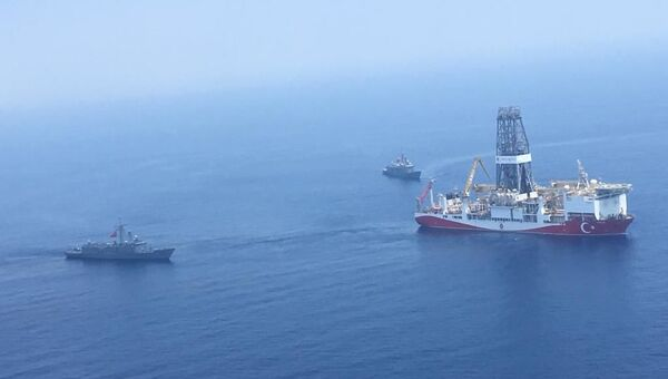 A handout photograph taken and released by the Turkish Defence Ministery on July 9,2019 shows a Turkish Navy warship patroling next to Turkey's drilling ship Fatih dispatched towards the eastern Mediterranean near Cyprus.  - Sputnik International