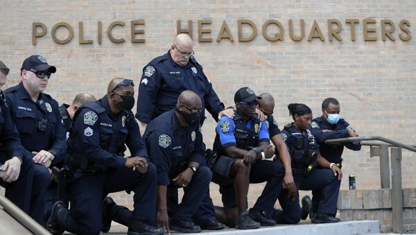 Members of the Austin Police Department kneel in front of demonstrators who gathered in Austin, Texas, Saturday, June 6, 2020, to protest the death of George Floyd, a black man who was in police custody in Minneapolis. Floyd died after being restrained by Minneapolis police officers on Memorial Day. - Sputnik International