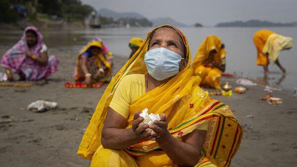 Hindu women perform rituals during a prayer ceremony to rid the world of coronavirus, on the banks of the river Brahmaputra in Gauhati, India, Friday, June 5, 2020 - Sputnik International