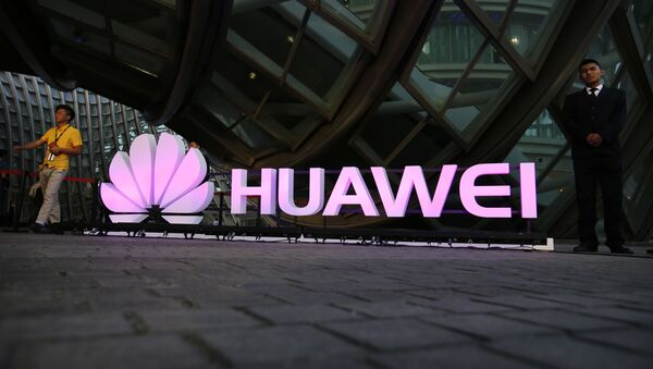 People walk past an illuminated logo for Huawei at a launch event for the Huawei MateBook in Beijing, Thursday, May 26, 2016 - Sputnik International