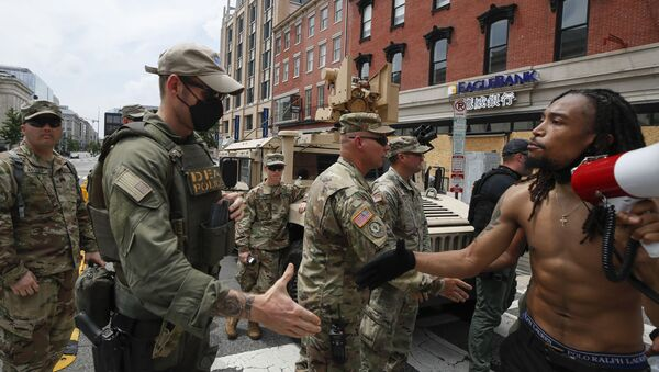 Aaron Covington of St. Louis, greets National Guard soldiers and DEA police as they protest Saturday, June 6, 2020, in Chinatown in Washington, over the death of George Floyd, a black man who was in police custody in Minneapolis. Floyd died after being restrained by Minneapolis police officers. (AP Photo/Alex Brandon) - Sputnik International