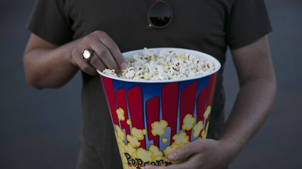 A moviegoer eats popcorn at Mission Tiki drive-in theater in Montclair, Calif., Thursday, May 28, 2020. - Sputnik International