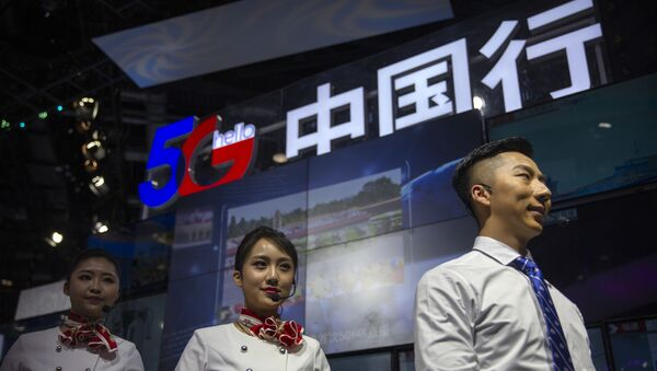 Staff members stand at a display for 5G services from Chinese technology firm China Telecom at the PT Expo in Beijing, Thursday, Oct. 31, 2019. - Sputnik International