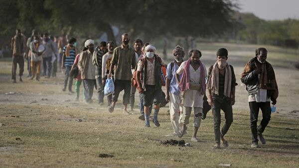 Indian migrant laborers and homeless people walk towards a bus as they are being evicted from the banks of Yamuna River where they have been squatting during lockdown in New Delhi, India, Wednesday, April 15, 2020 - Sputnik International