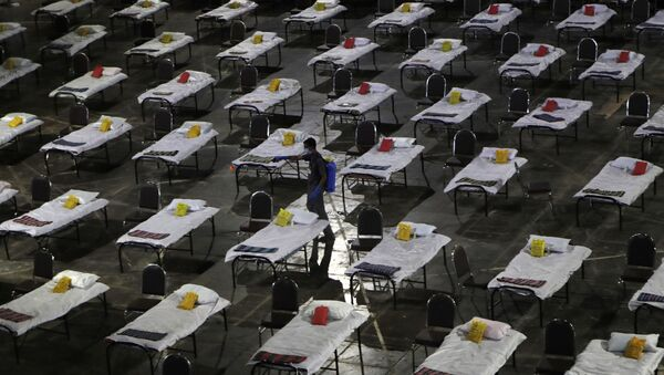 A civic worker sprays disinfectant on beds at a special temporary hospital facility for COVID-19 patients in Mumbai, India, Friday, April 10, 2020 - Sputnik International