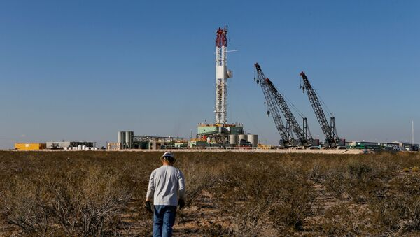 An oil worker walks towards a drill rig after placing ground monitoring equipment in the vicinity of the underground horizontal drill in Loving County, Texas, U.S., November 22, 2019. Picture taken November 22, 2019 - Sputnik International