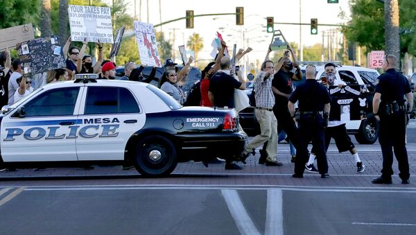 Protesters demanding police reform walk past Mesa police officers blocking a street, Tuesday, June 9, 2020, in Mesa, Ariz. The protest is a result of the death of George Floyd, a black man who died after being restrained by Minneapolis police officers on May 25 - Sputnik International