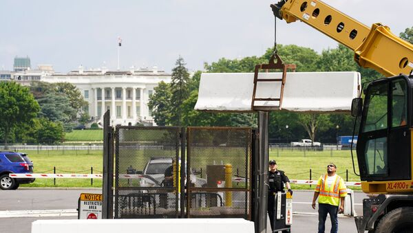A pedestrian ducks under a concrete barrier while a crane removes barriers from around the White House as workers begin to take down fences that were installed during the recent demonstrations against racial inequality in the aftermath of the death in Minneapolis police custody of George Floyd, on the streets near the White House in Washington, U.S., June 10, 2020 - Sputnik International