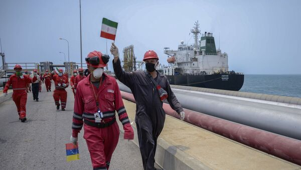 A worker of the Venezuelan state oil company PDVSA waves an Iranian flag as the Iranian-flagged oil tanker Fortune docks at the El Palito refinery in Puerto Cabello, in the northern state of Carabobo, Venezuela, on May 25, 2020 - Sputnik International