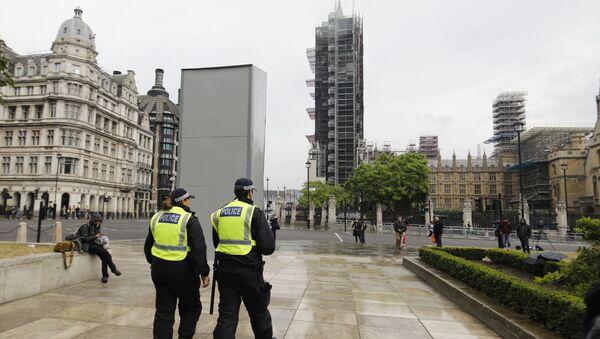 Police officers walk past a boarded-up statue of British wartime Prime Minister Winston Churchill on Parliament square in central London on June 12, 2020 - Sputnik International