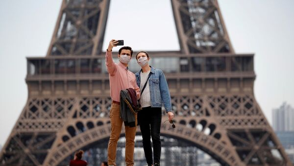 People wearing face masks take a selfie at Trocadero square near the Eiffel Tower, as France began a gradual end to a nationwide lockdown due to the coronavirus disease (COVID-19) in Paris, France, May 16, 2020 - Sputnik International